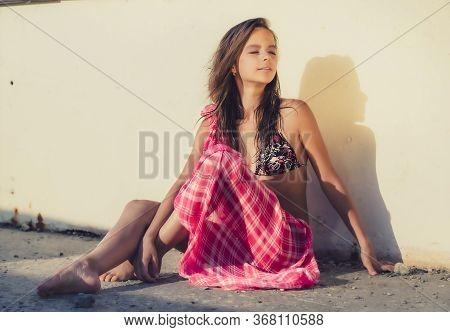 Beautiful Young Girl In Bright Bikini Swimsuit Sitting Near Wall. Fashionable Resort. Girl Sunbathes