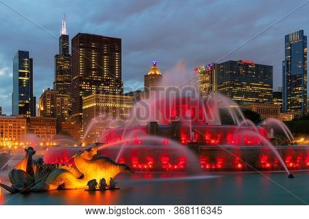 Buckingham Fountain And Chicago City At Night With Skyscrapers Of Chicago, Illinois, Usa.
