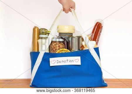 Set Of Grocery Food For Needy In Crisis, Pasta, Beans, Canned Food, And Others In Blue Shopping Bag