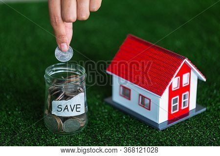 Red Roof House And A Coin In A Glass Bottle With A Hand Is About To Coin Ideas For Planning To Save