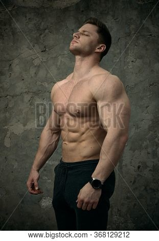 Handsome Muscular Man Posing On Concrete Wall Background. The Concept Of Fitness, Bodybuilding, Heal