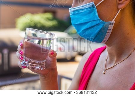 Girl In Blue Medical Mask Outdoor Holds In Hand A Glass Of Still Pure Water. Drinking Spirits In Pos