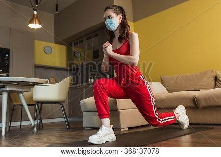 Sportive Woman In Medical Mask And Clenched Hands Exercising On Fitness Mat