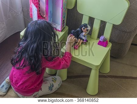 Toronto, Canada, April 2020 - Little Girl Playing With Doll At Home During Coronavirus Pandemic Conf