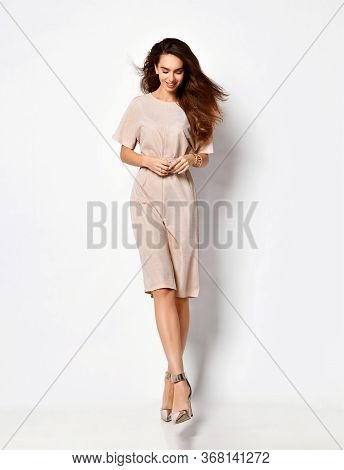 Young Lady Posing In A Light Pink Knee-length Dress With A Belt And Silver High Heels. Style And Fas