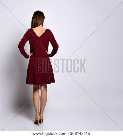 Rear View Of A Pretty Young Woman In A Dark Elegant Dress Posing In High Heels. Elegance, Glamor, St