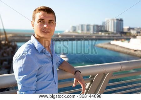 A Man In A Blue Shirt Stands On A Bridge Over A River. Caucasian Man 30-35 Years Old In A Blue Shirt