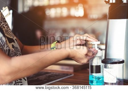 Woman Uses Her Hand To Press Hand Sanitizer Bottle To Clean Her Hand In Coffee Shop. Hand Sanitizer