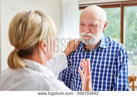 Woman as a family doctor comforts a senior man with dementia in the consultation