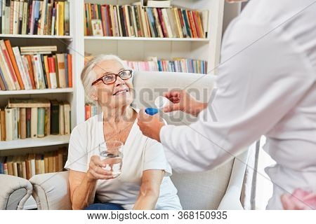 Nurse distributes medication to senior woman in assisted living