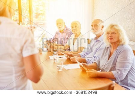 Group of seniors with laptop and tablet PC at computer course in retirement home