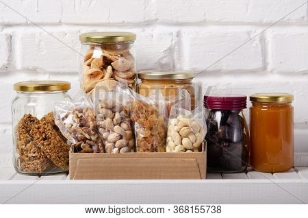 Set Of Long Storage Term Mostly Dry Sweet Energy Foods On Pantry Shelf On Brick Wall Background