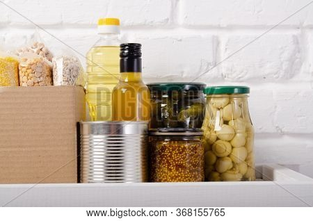 Set Of Non-perishables On Pantry Shelf Prepared For Disaster Emergency Conditions On Brick Wall Back