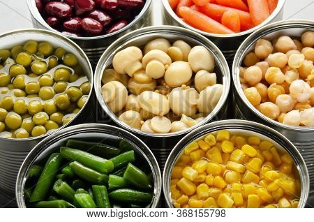 Canned Vegetables In Opened Tin Cans On Kitchen Table. Non-perishable Long Shelf Life Foods Backgrou