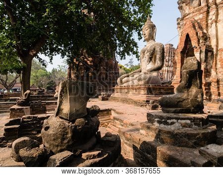 A Stone Figure Of Buddha In The Ruins Of A Royal Buddhist Temple, Ayuthaya Unesco Archaeological Par