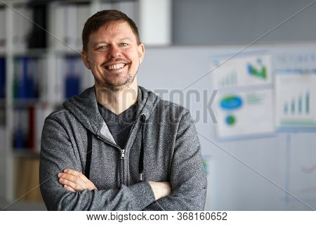 Happy Man In Casual Wear Is Standing And Smiling. Man During Quarantine Arranged Workplace In An Apa