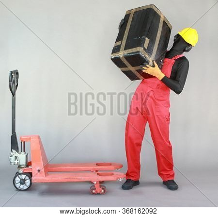 Front view of anonymous worker dealing with heavy package at manual pallet truck.Correct body position.