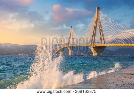 Modern Bridge at the evening sunset time with waves splash. Rion-Antirion Bridge, Greece, Europe. The Rion-Antirion Bridge in Greece one of the longest of the fully suspended type brige