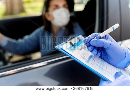 medicine, quarantine and pandemic concept - close up of doctor or healthcare worker in protective medical gloves writing to clipboard and woman waiting for coronavirus test in her car