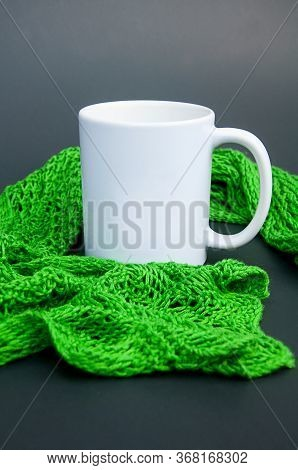 White Coffee Mug Nestled In Green Lace Scarf On A Dark Background With Copy Space For Text Or Graphi