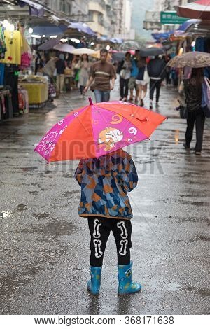 Kowloon, Hong Kong - April 23, 2017:  Child With Red Umbrella At Street Market Rainy Day In Kowloon,