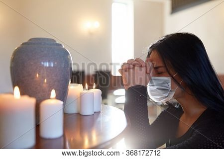 people and mourning concept - sad woman wearing face protective medical mask with cinerary urn and candles praying at funeral in church