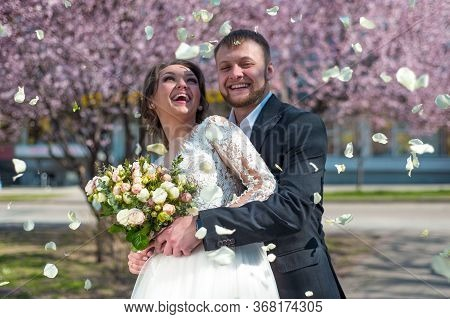 Happy Couple Of Bride And Groom, Against The Background Of Pink Spring Floral Sakura, Newlyweds, Spr