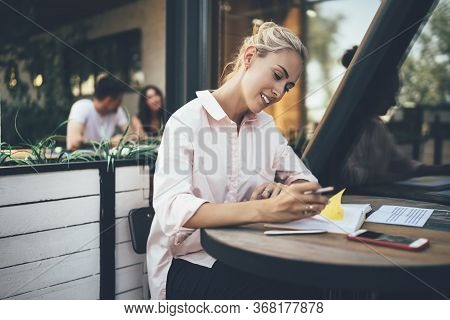 Woman With Diary Sitting On Cafe Terrace In Diary While Making Plans For Day