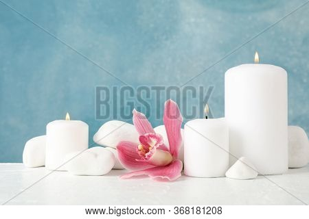 Beautiful Orchid, Candles And Spa Stones On White Table, Space For Text