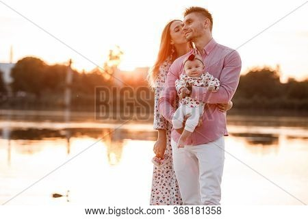 Happy Young Family Near Lake, Pond. Family Enjoying Life Together At Sunset. People Having Fun In Na