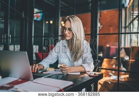 Blond Woman Using Laptop In Cafe. Work On Freelance