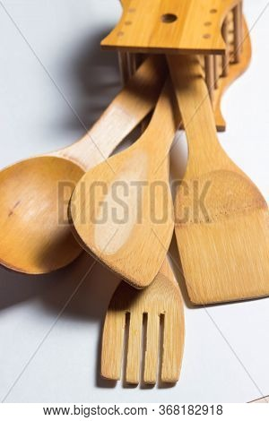 Four Wooden Cutlery Lie On A White Background. Wooden Spoon, Wooden Fork. And Two Wooden Spatulas