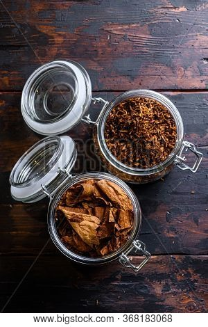 Cigar And Pile Of Tobacco Leaves Of Dried Tobacco In Glass Jars On Rustic Wood Dark Table Top View S