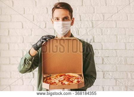 Hipster Guy Courier In Medical Face Mask And Gloves Hold Cardboard Pizza Box In Hands. Happy Man Del