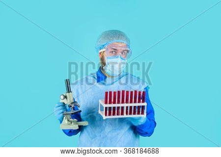 Laboratory Work. Man In Medical Mask And Glasses Hold Test Tubes. Doctor In Protective Suit And Mask