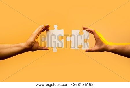 Closeup Hand Of Connecting Jigsaw Puzzle. Business Solutions, Success And Strategy Concept. Two Hand