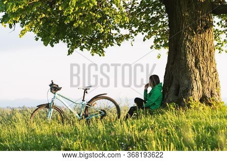 A lonely girl sits under a big old tree near a bicycle. Green summer landscape on city contrside