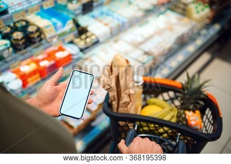 Man choosing dairy products in grocery store