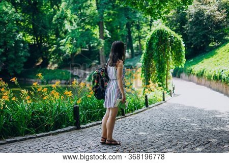 Sofia Park, Uman. Young Woman With A Backpack Walking In The Park. Girl In A Sundress And A Tourist