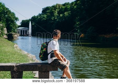 Sofia Park, Uman. Handsome Man With A Backpack Sitting On A Stone Bench In The Park. Young Man On Th