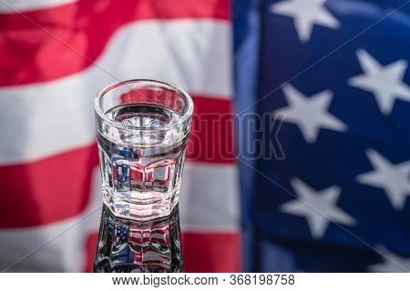 Vodka In Shot Glass On Mirror Background With American Flag Reflected In It. Independence Day Drink
