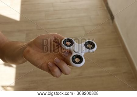 A Guy Performs A Trick With The Finger Spinner, A Pastime Very Popular Among The Childs