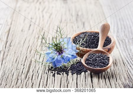 Black cumin seeds with flower on wooden board