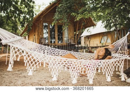 Woman Relaxing In The White Handmade Macrame Hammock On Tropical Beach. Travel, Leisure And Vacation