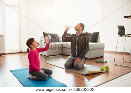 Father And Daughter Are Training At Home. Workout In The Apartment. Sports At Home. They Sit On Yoga