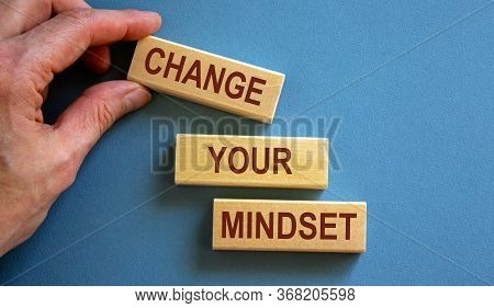 Wooden Blocks Form The Words 'change Your Mindset' On Blue Background. Male Hand.