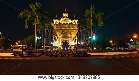 Auto Rickshaw In Front Of Victory Gate Patuxai War Memorial At Night  Vientiane Laos