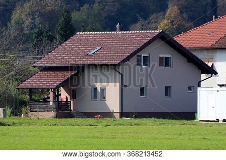 Newly Built Small Suburban Family House With Front Porch And New Roof Tiles Surrounded With Old Hous