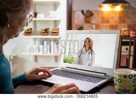 telemedicine concept elderly woman in an online consultation on video call from her kitchen taking her blood pressure