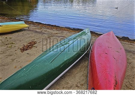 Colourful Canoe Lying On The Beach In Lake Muskoka